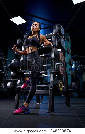 From Below View Of Female Bodybuilder Posing Near Stand With Sports Equipment, Touching Braids. Srto