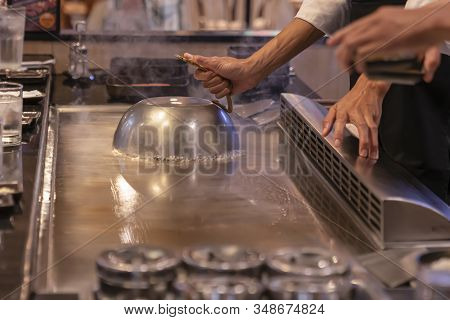 Teppanyaki, Japanese Cuisine. Cooking A Dish Covered With A Lid On A Roasting Surface In A Japanese