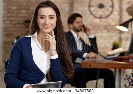 Portrait of confident young businesswoman sitting in office, smiling, looking at camera.