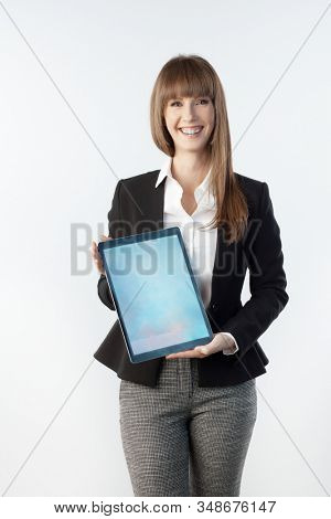 Happy white young businesswoman showing large business tablet with blank screen. Woman with happy smile, isolated on white.