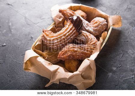 Churros In A Paper Bag With Sugar And Chocolate Sauce On Black Background. Top View. Top Down Plate