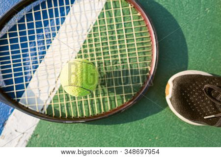 Yellow Tennis Ball On The Floor Of The Tennis Court With Racket And Shoe