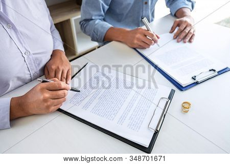 Young Couple In The Courthouse Filing Pen To Signing Divorce Papers Or Premarital Agreement, Decidin