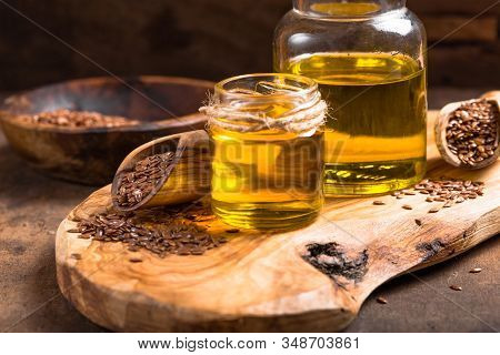 Flax Seeds Oil And Raw Seeds On Wooden Background. Flax Seeds And Oil In Glass Bottle