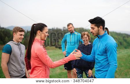 Large Group Of Fit And Active People Resting After Doing Exercise In Nature.