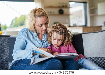 A Cute Small Girl With Mother On Sofa Indoors At Home, Reading Book.