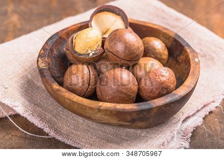 Pile Macadamia Nuts Open Kernels And Shells In Burlap Bag On Wooden Background. Macadamia Nuts Close