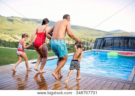 Rear View Of Family With Two Small Children By Swimming Pool Outdoors.
