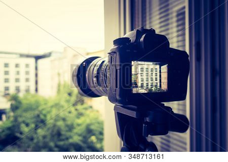 Surveillance And Stalking Concept: Camera With Telephoto Lens On Tripod, Observing A House