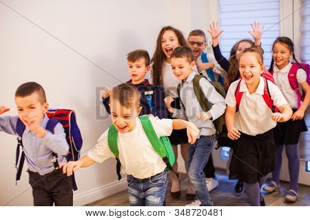 Happy School Kids Running In Elementary School Hallway, Front View