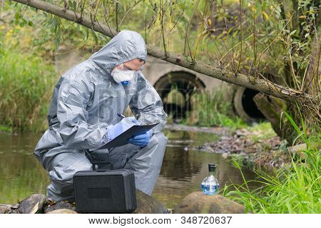 A Specialist, In A Protective Suit And Gloves, Working With Toxic Substances, Records The Results Of