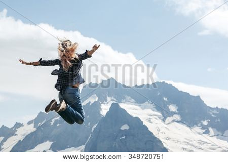 Woman hiker jumping on top of the mountain over blue skies, freedom and joy