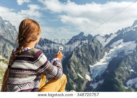 Back view of child girl hiker holiding spring flower and enjoying beautiful mountains landscape
