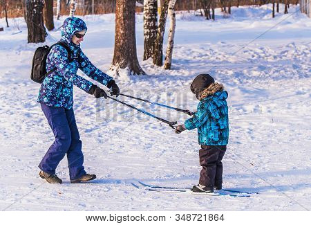 Beautiful Woman With A Child On A Ski Trip. Mom Teaches Son To Ski