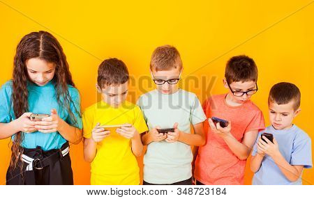 Group Of Kids Using Digital Mobile Phone