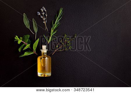 Essential Oil Of Herbs For Spa Treatments. Bottle Of Natural Oil With Ingredients On Black Backgroun