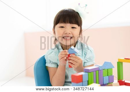 Cute Little Asian Girl Playing With Colorful Toy Blocks While Sitting At Table And Smiling At The Ca