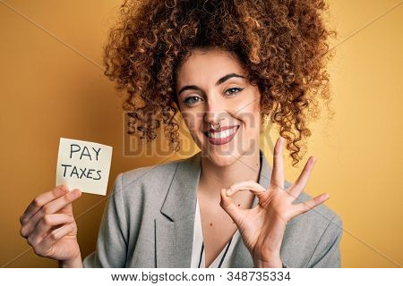 Young business woman with curly hair holding pay taxes to goverment reminder over yellow background doing ok sign with fingers, excellent symbol