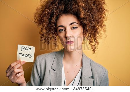 Young business woman with curly hair holding pay taxes to goverment reminder over yellow background with a confident expression on smart face thinking serious