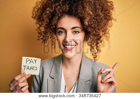 Young business woman with curly hair holding pay taxes to goverment reminder over yellow background very happy pointing with hand and finger to the side