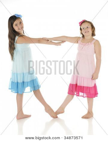 Two happy elementary girls dancing in identical dresses except one is blue, the other pink.  On a white background.