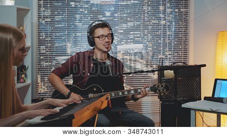 Recording Hit Song In Home Studio: Young Man In Headphone Singing And Playing Guitar While The Piani