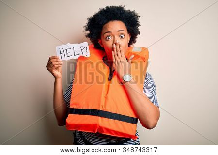Young African American afro woman with curly hair wearing lifejacket holding help paper cover mouth with hand shocked with shame for mistake, expression of fear, scared in silence, secret concept