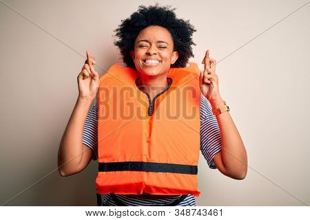 Young African American afro woman with curly hair wearing orange protection lifejacket gesturing finger crossed smiling with hope and eyes closed. Luck and superstitious concept.