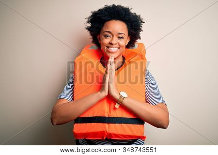 Young African American afro woman with curly hair wearing orange protection lifejacket praying with hands together asking for forgiveness smiling confident.