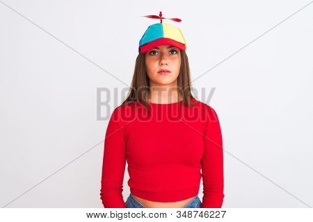 Young beautiful girl wearing fanny cap with propeller standing over isolated white background with serious expression on face. Simple and natural looking at the camera.