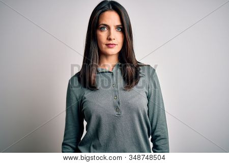 Young brunette woman with blue eyes wearing casual green sweater over white background with serious expression on face. Simple and natural looking at the camera.