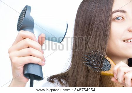 Closeup Of Female Hands Are Holding Comb And Hairdryer. Young Smiling Woman Is Drying Hair After Was