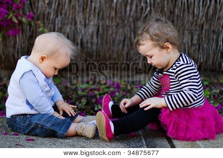 Baby boy and toddler girl sitting and playingoutdoors