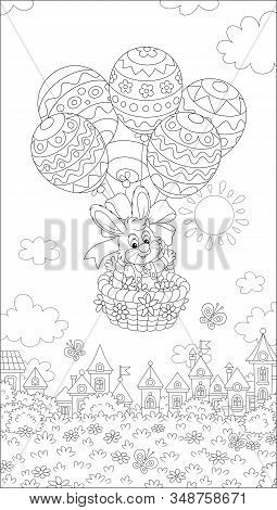 Little Easter Bunny Flying In Its Holiday Basket With Decorated Balloons Above A Small Toy Town On A