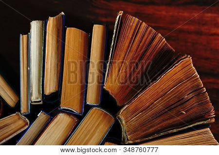 Old And Well Used Hardback Books Or Text Books In A Book Shop Or Library. Many Books Piles. Hardback