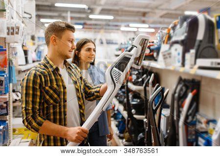 Couple choosing vacuum cleaner, electronics store
