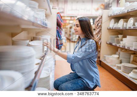 Young woman choosing plates in houseware store