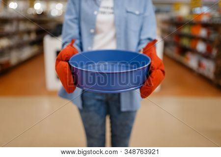 Woman in gloves holds bowl, houseware store