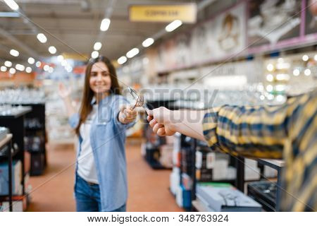 Young couple fencing in houseware store