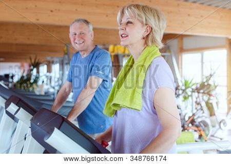 Senior couple exercising together on the treadmill in a fitness gym having fun in the process