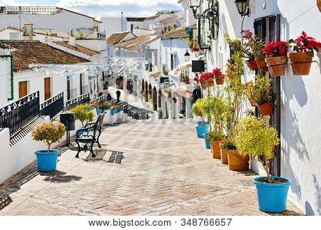 Idyllic Scene Picturesque Street Small White-washed Village Of Mijas. Path Way Decorated With Hangin