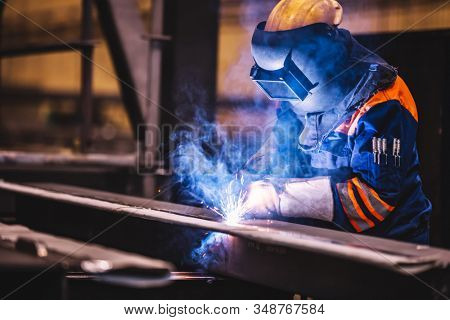 Worker welding in a factory. Heavy industry, welder work