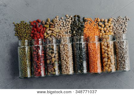 Indoor Shot Of Organic Grains, Nuts, Seeds In Transparent Glass Jars Spilled On Grey Surface. Food P
