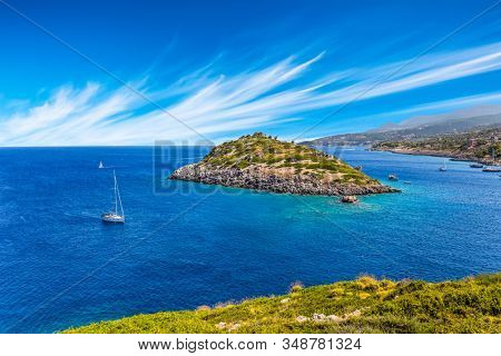 Holiday in Greece, island of Zakynthos. Bright blue sea water reflects coastal cliffs. Snow-white yacht sails along the rocky shores of the island. The concept of marine, active and resort recreation