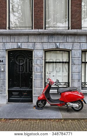 Amsterdam, Netherlands - July 10, 2017: Red Piaggio Vespa Scooter Parked In Amsterdam, Netherlands.