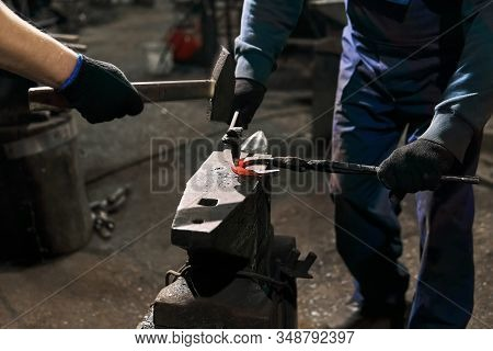 Blacksmith With Striker Forges A Horseshoe On The Anvil With Forging Chisel, Close-up