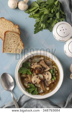 Mushroom Soup Of Champignons And Lentils In A White Plate On A Light Blue Background