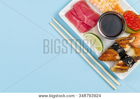 Traditional Japanese Sushi Set On A White Plate Isolated On A Blue Background. Tasty Set Of Sushi, N