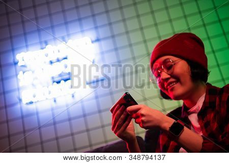 Teen Girl Exciting Playing Smart Phone In A Room Lit With Neon Color At Home.