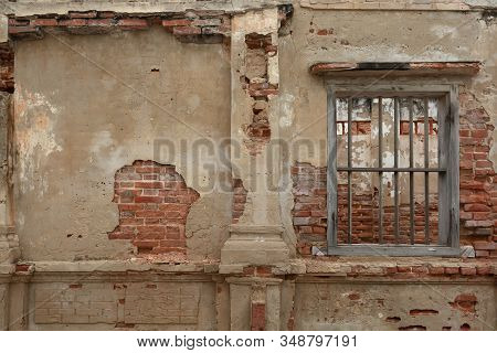 Rendered Concrete Wall With Exposed Red Brick And Wooden Jail Cell Like Window. Abstract Texture Bac